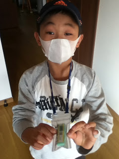 "Koutarou Sugano, 9, wears a mask and a ""glass badge"" radiation monitor last month."
