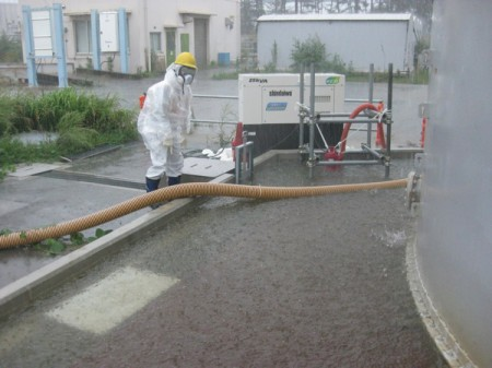 [Photo] Overflowed tank area / Worker in the protective clothing under the typhoon
